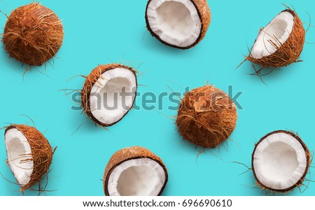 Coconut pattern on a blue background. Half and whole coconuts. Repetition concept. Top view