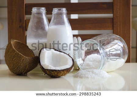 Coconut products. Cracked open coconut with meat cut in half, grounded flakes in a mason jar, flour and fresh milk in glass bottles on a table with wooden background.