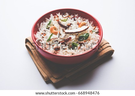 Coconut Rice - South Indian recipe using leftover cooked Basmati rice, served in a red bowl over moody background, selective focus