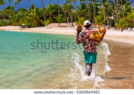 Coconut saler walking by the sea in the famous Juan Dolio Beach of Dominican Republic with the atmospheric background of palm trees.