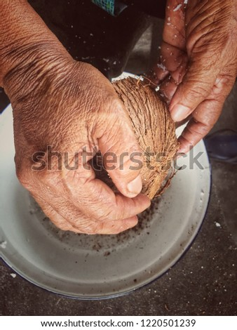 Coconut scraping with the hands of people.