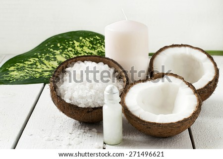 Coconut Spa concept: coconut, coconut oil, sea salt and candle with the scent of coconut on a white background