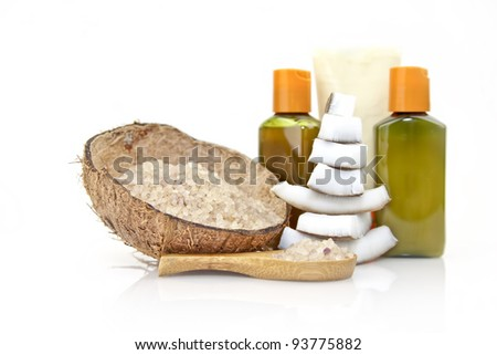 coconut spa salt in coconut shell with wooden spoon and spa oil