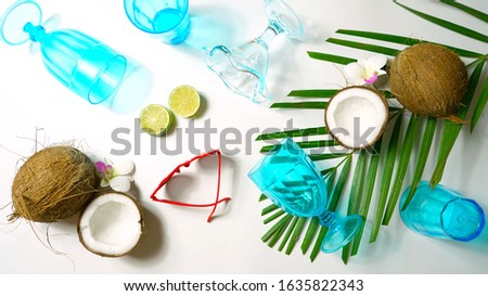 Coconut summertime entertaining theme flat lay creative layout overhead with shadows from blue drinking glasses cast over table.