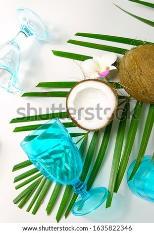 Coconut summertime entertaining theme flat lay creative layout overhead with shadows from blue drinking glasses cast over table. Vertical close up.