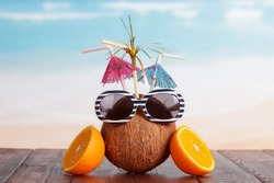 Coconut with straw, umbrellas, sunglasses and a part of orange on a brown table against the sea.