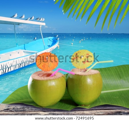 coconuts straw cocktails in tropical caribbean turquoise beach with boat [Photo Illustration]