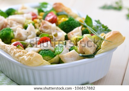 Cod fillet on mixed vegetables in season baked on puff pastry