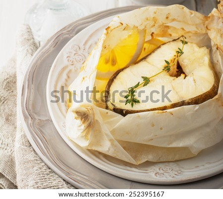 Cod fillets  baked in parchment paper with slices of lemon and a sprig of thyme on light dishes. Selective focus. Concept of healthy food.