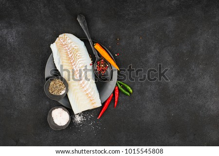 Cod fillets on a black ceramic plate for the preparation of a healthy dish with the addition of pink pepper, hot pepper, spinach, lemon, salt on a simple black background. Top view. Copy space
