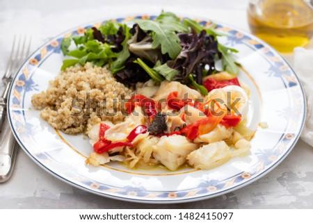 cod fish with quinoa and fresh salad on dish on ceramic dish