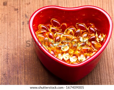 Cod liver oil omega 3 gel capsules isolated on pastel background. Vitamin d pils. Pils in Hearth shape bowl