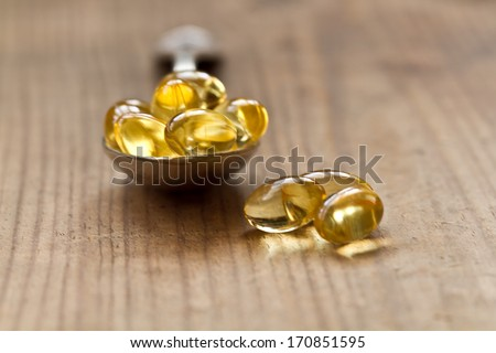Cod liver oil omega 3 gel capsules isolated on wooden background. Vitamin d capsuls. Fish oil supplements - stock photo