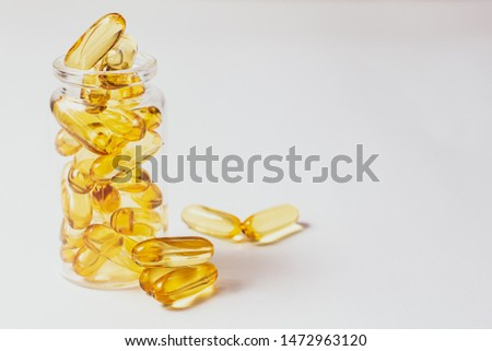 Cod liver oil omega 3 gel capsules with vitamin E in glass jar isolated on white background with copy space for your text. Healthy life style and health care concept.