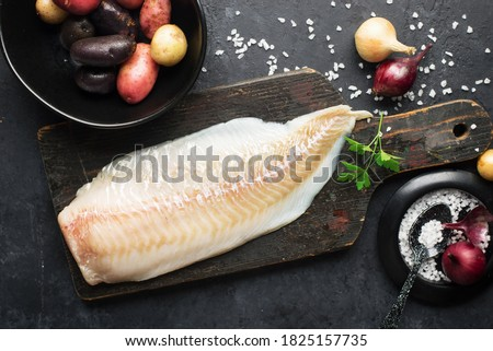 Cod white fish potatoes dish ingredients for healthy comfortable home food. Raw white fish fillet in a baking dish on a dark background. Top view. ストックフォト ©