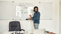 Code academy online. Young serious bearded male teacher wearing glasses pointing at whiteboard and teaching HTML CSS, giving lesson online. Focus on a man. E-learning. Distance education. Stay home