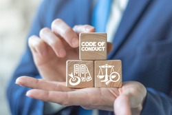 Code of conduct business concept on wooden blocks in businessman hands. Ethics and respect in working collective.