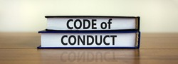 Code of conduct symbol. Concept words 'Code of conduct' on books on a beautiful wooden table, white background. Business and code of conduct concept. Copy space.
