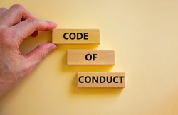 Code of conduct symbol. Concept words 'Code of conduct' on wooden blocks on a beautiful white background. Businessman hand. Business and code of conduct concept. Copy space.