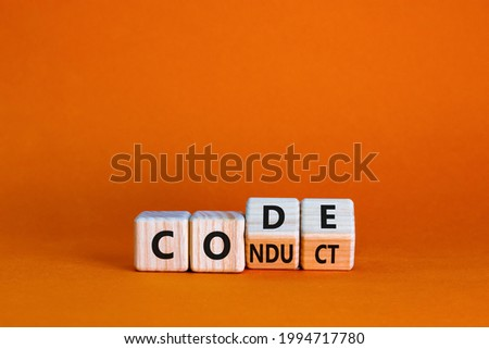 Code of conduct symbol. Turned the wooden cube and changed the word code to conduct. Beautiful orange background. Business and code of conduct concept. Copy space. Сток-фото ©