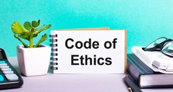 CODE OF ETHICS is written on a white card next to a potted flower, diaries and calculator. Organizational concept