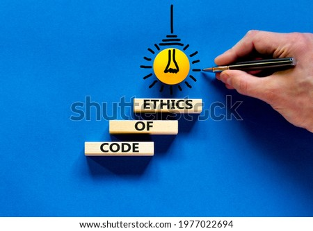 Code of ethics symbol. Concept words 'Code of ethics' on wooden blocks on a beautiful blue background. Businessman hand, light bulb icon. Business and code of ethics concept. Copy space. Stock photo ©