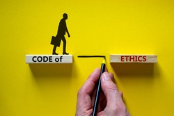 Code of ethics symbol. Wooden blocks with words 'Code of ethics'. Businessman hand. Businessman icon. Beautiful yellow background, copy space. Business and code of ethics concept.