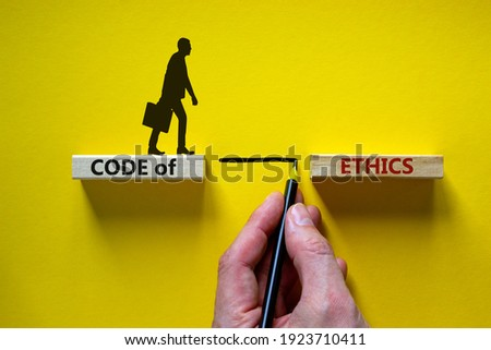 Code of ethics symbol. Wooden blocks with words 'Code of ethics'. Businessman hand. Businessman icon. Beautiful yellow background, copy space. Business and code of ethics concept. Сток-фото ©