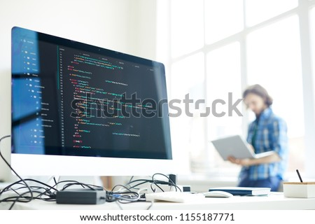Coded data on computer screen at workplace of modern programmer networking on background