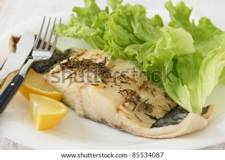 codfish with lemon and salad - stock photo