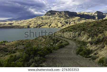 Cody, Wyoming, USA. The arid landscape of Buffalo Bill State Park with the Shoshone River flanked by rolling landscape and mountains  at dawn on a summer day near Cody, Wyoming, USA.