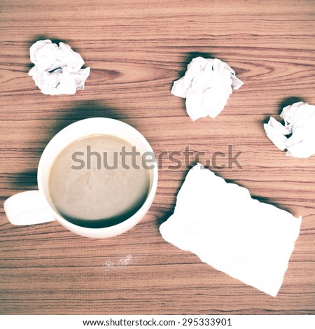 coffe cup and crumpled for idea on wood background vintage style