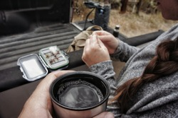 Coffe in a thermos cup with truck bed and a flybox in the background. Gearing up for flyfishing.