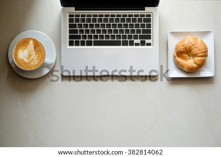 coffe, laptop and croissants to show a business breakfast on the marble floors in morning  #382814062