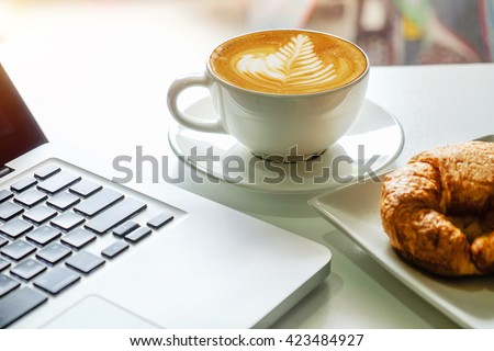 coffe, laptop and croissants to show a business breakfast on the office table in morning #423484927