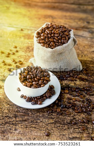 Coffee. A coffee cup with grains and a coffee bag on a wooden table.