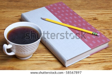 Coffee and a book waiting to be opened, a pencil waiting to take notes, all sitting on a beautiful wood table