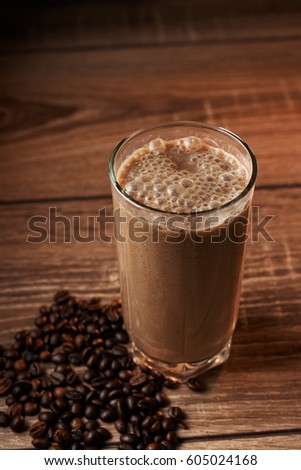 Coffee and banana smoothie in a glass on a wooden background, coffee beans #605024168