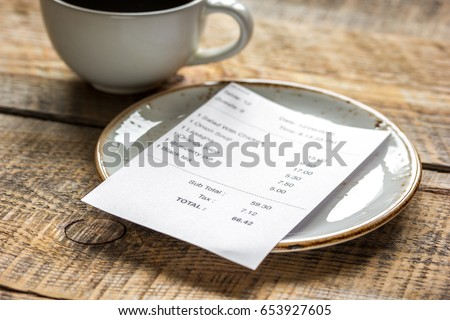 coffee and check on cafe wooden desk background