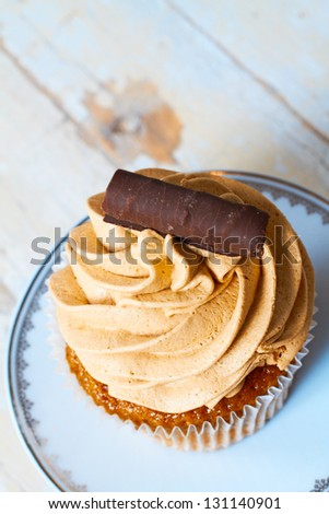 Coffee and chocolate cream cupcake with a swirl on a white plate against grunge wooden background