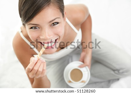 Coffee and cookie woman. Beautiful Asian / Caucasian woman enjoying coffee with a cookie.