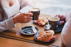 coffee and croissants in cafe, hands of couple closeup