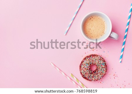 Coffee and fresh pastry of chocolate donut on pink pastel table top view. Flat lay. Cozy breakfast