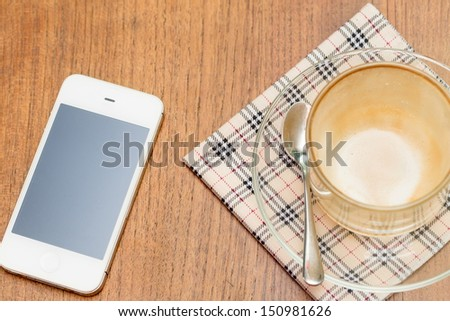Coffee and mobile phone on a Wooden Table