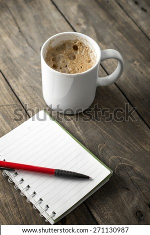 coffee and notebook on working desk, close up