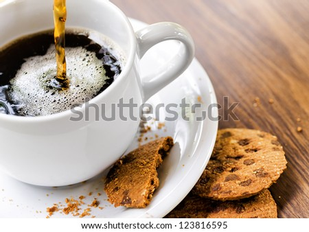 Coffee and oatmeal cookies on wooden table.