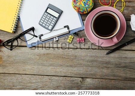 Coffee and office supplies on grey wooden background