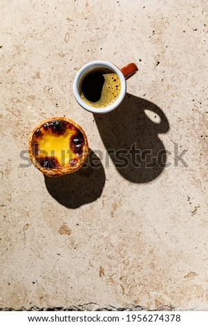 Coffee and Pastel de Nata Fresh baked Portuguese egg custard Tart on beige stone background Foto stock ©