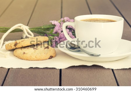Coffee and purple flower witn bean and white glass, dish, cloth on brown wooden