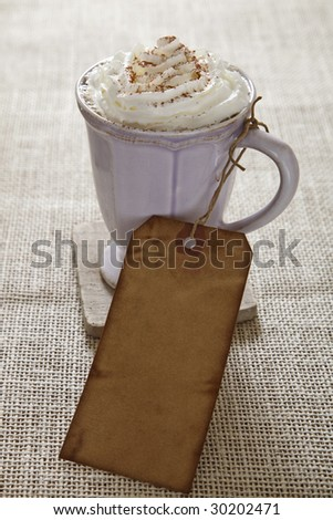 coffee and whipped cream with old-fashioned paper price tag on burlap background